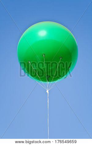 Green big balloon over a blue sky