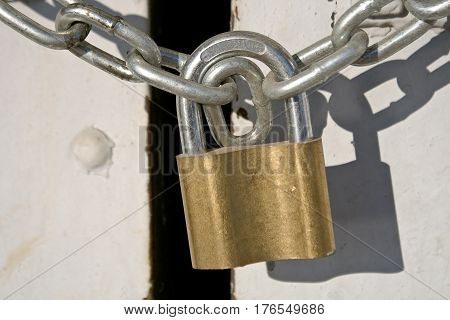 Padlock with chain on old white door