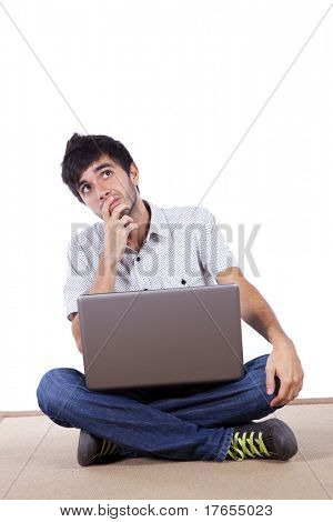 Young man working with his laptop on the home floor (isolated on white)