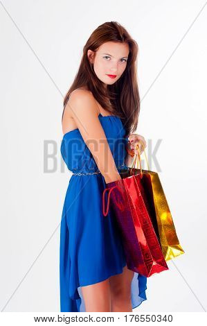Beautiful red-haired woman with freckles holding shopping bags, isolated over white studio background