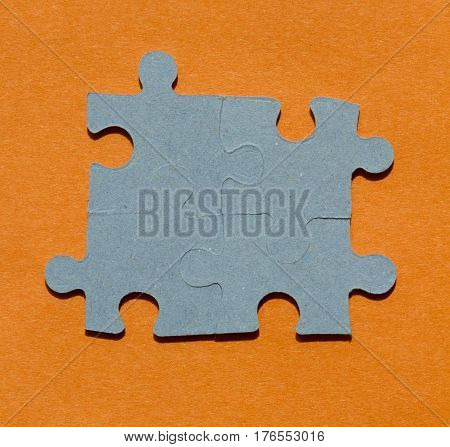 Jigsaw puzzle pieces on bright orange background square
