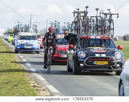 Le Gaut Saint DenisFrance- March 72016: A cyclist of Team Giant-Alpecin discussing with a staff member while riding next to his team car in Eure et Loire region of France during the first stage of Paris-Nice 2016.
