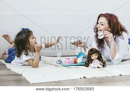 Young Beautiful Woman Mother And Daughter With Toy Dishes, Sweets, And Dolls Playing Tea Party