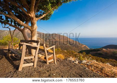 Bali Island Crete Greece - June 25 2016: Beautiful morning scenery with two wooden benches near the tree. Benches are installed on the viewpoint with astonish view on Mediterranean sea and the mountains near village Bali that is located on the coast.