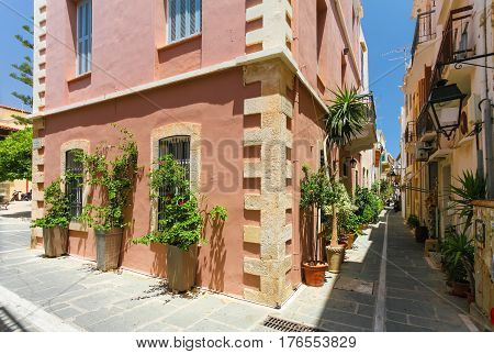 Rethymnon Island Crete Greece - June 23 2016: The narrow street of the old town's part of city Rethymnon and red colored house with plants and flowers in the big pots in hot sunny summer day.