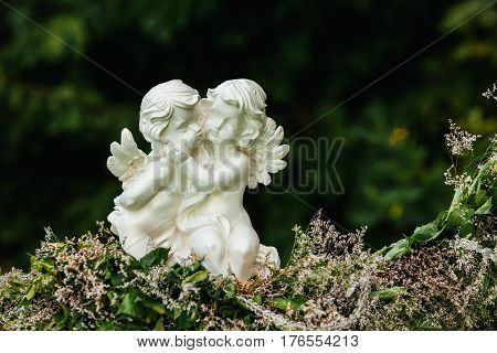 Stone sculpture of two hugging angels on flowers garland