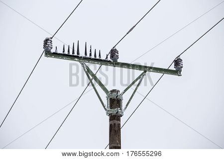 Electrical pylons high voltage wires in winter covered snow and ice