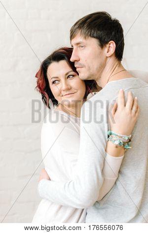 Indoors beautiful, young, loving couple gently hugs
