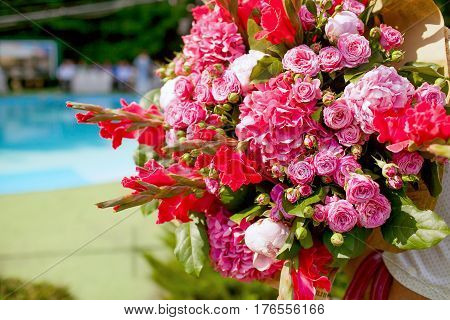 Wedding decorating bouquet of pink and red roses peons and irises, closeup