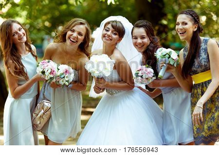 Smiling Bride Poses With Happy Bridesmaids With Bouqets In Their Arms