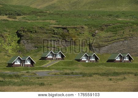 Landscape with Traditional iclandic wooden houses for turists on rock at the bottom of mountain.