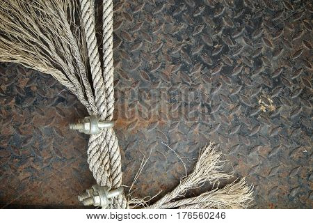 Old Ropes with U-Bolt Clamp on a rusty metal background