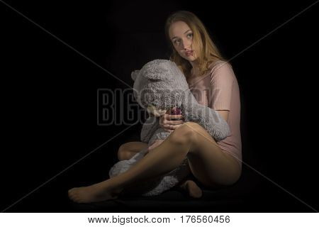 Young girl with big teddy on black background