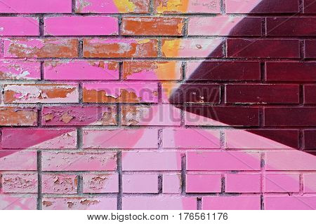 Old colorful (pink purple orange and burgundy) paint with cracks on brick wall as background texture