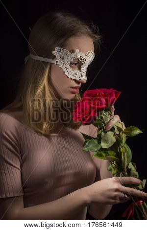Portrait of a shy girl wearing mask and red roses on black background
