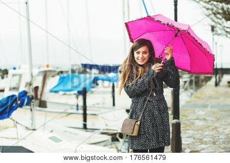 Young 20-25 year old woman holding pink umbrella under the rain