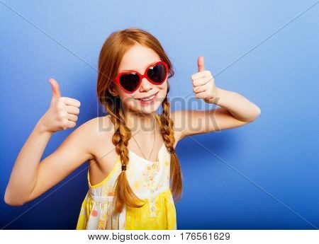 Studio shot of young preteen 9-10 year old redhead girl wearing heart shape sunglasses, standing against blue purple background, big thumbs up
