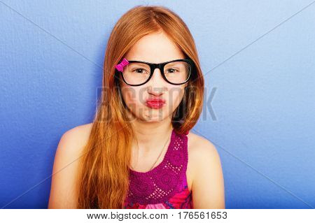 Studio shot of young preteen 9-10 year old girl wearing eyeglasses, standing against blue purple background