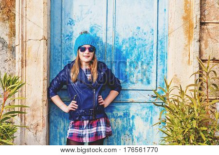 Outdoor fashion portrait of preteen 10-11 years old girl wearing blue leather jacket, hat and sunglasses