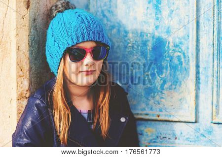 Outdoor fashion portrait of preteen 10-11 years old girl wearing blue hat and sunglasses