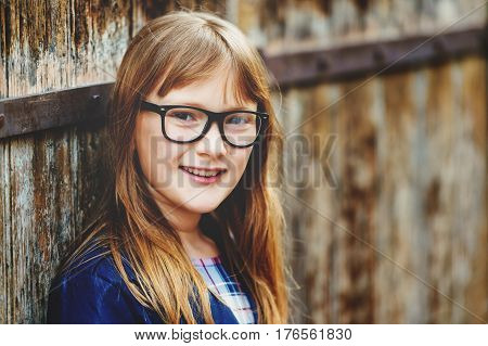 Outdoor portrait of a cute little 9 year old girl wearing eyeglasses standing against old wooden background