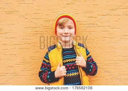 Outdoor portrait of cute 6-7 year old boy wearing warm pullover, waistcoat and colorful hat