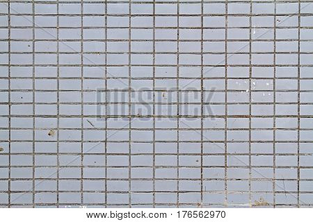 Mosaic tiles on the facade of a house. Architectural background made of grey mosaic wall