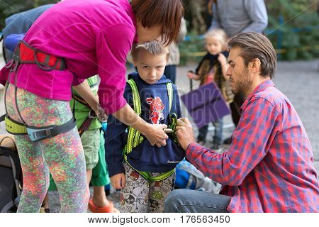 Family of father mother and son putting on gear preparing for climb the wall. Family Climbing Competitions Mother, Father and Me , Dnipro, Ukraine, September 18, 2016