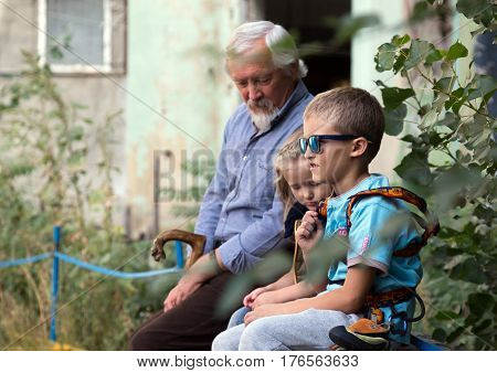 Mature Grandfather and two Grandchildren little baby girl and elder boy sitting and talking while watching the climbing competitions. Family Climbing Competitions Mother, Father and Me , Dnipro, Ukraine, September 18, 2016