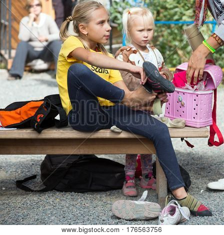 Little participants of climbing competitions putting on climbing shoes preparing for climb. Family Climbing Competitions Mother, Father and Me , Dnipro, Ukraine, September 18, 2016