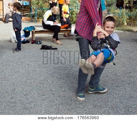 Father and son having fun on climbing competitions, man swinging boy holding him for climbing harness. Family Climbing Competitions Mother, Father and Me , Dnipro, Ukraine, September 18, 2016