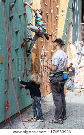 Little participants of climbing competitions and father warming up and trying holds of climbing wall. Family Climbing Competitions Mother, Father and Me , Dnipro, Ukraine, September 18, 2016
