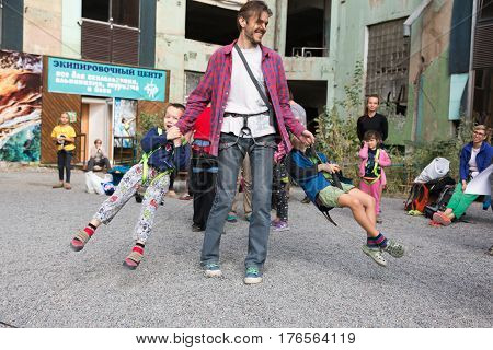 Father and children having fun on climbing competitions, man swinging boys around holding them for climbing harness. Family Climbing Competitions Mother, Father and Me , Dnipro, Ukraine, September 18, 2016