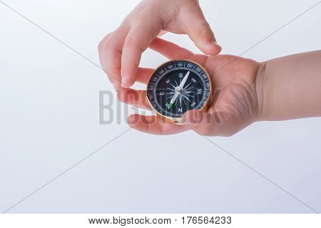 Hand Holding A Compass  On White Background