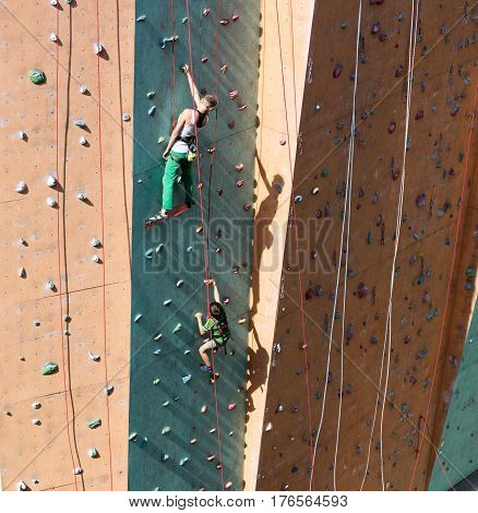 Woman Mother in white shirt and green pants and her son boy climbing vertical wall togeth
