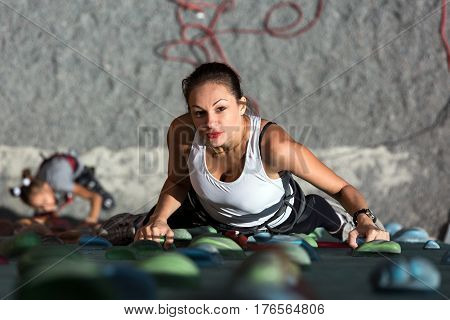Female Climber in white shirt smiling and looking up and her Daughter below starting her try on rock climbing wall