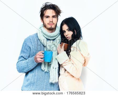 lovely cute couple holding colorful cups. Bearded caucasian man with moustache in knitted blue sweater and scarf with brunette pretty girl in beige robe drink coffee or tea isolated on white