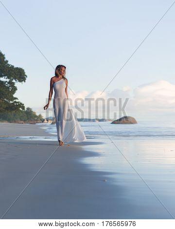 Beautiful, sexy blonde woman walks at tropical beach, long dress