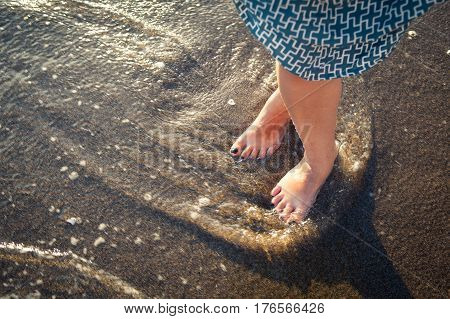 Beautiful bare feet on the beach. Sea foam washes female legs. Image of feet in the sand on the shore in the wave. Sunshine on the ocean in the wave. Summertime holidays Sea waves and sand.