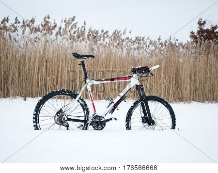 The mountain bike stay in snow. Lost path in deep snowdrift. Snow melting on dark off road tyre. Winter weather in the field.