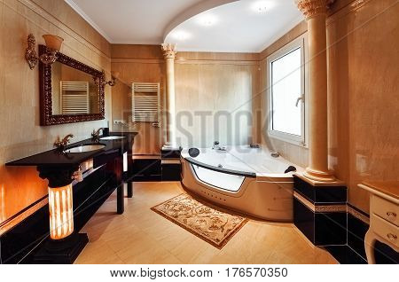 Luxurious bathroom in classic style with columns of Corinthian. Bathroom with two washbasins and a Jacuzzi. The floors and walls with marble.