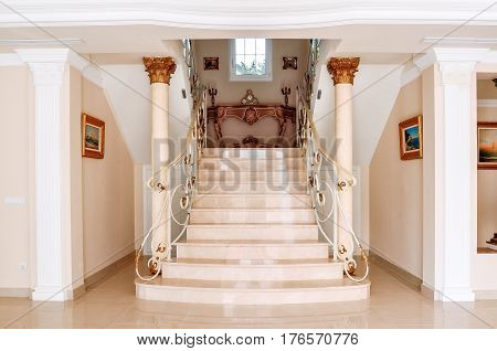 Luxurious staircase with marble steps and decorative and ornamental iron railings. On the top are decorating furniture in neoclassical style a table with candles. Corinthian Column Style.