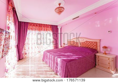 Luxurious bedroom with a bright pink color with large windows. Beautiful tulle and curtains. In the room the marble floors have a large luxurious bed.
