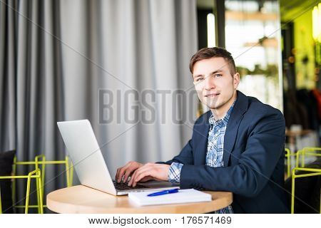 Happy Satisfied Young Man Working On Laptop And Looking At Camera In Office