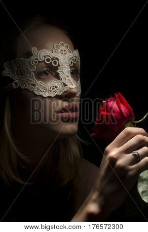 Portrait of a shy girl wearing mask and red rose on black background