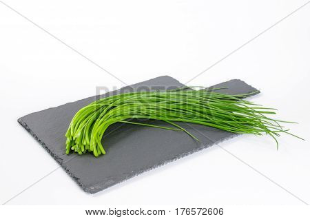 Spring onions laying on dark shale cutting board on white background
