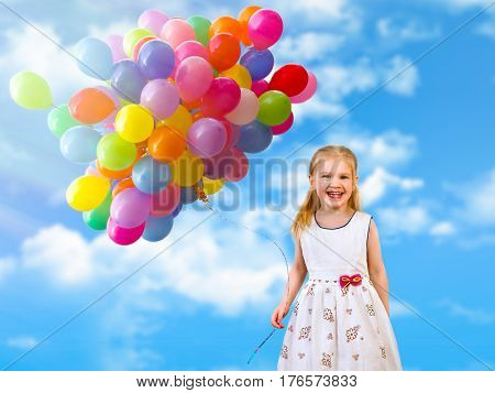 child and a lot of balloons on a background of blue sky and clouds. Portrait of happy little girl with colorful balloons