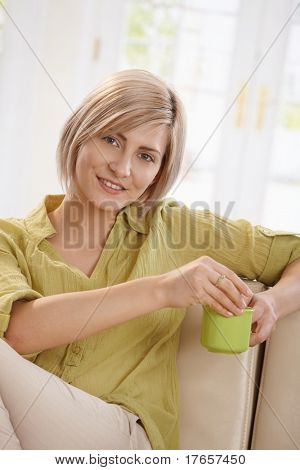 Portrait of young blonde woman sitting on couch at home, drinking tea, looking at camera smiling.?
