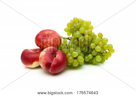 Chinese flat peaches and a bunch of green grapes on white background. Horizontal photo.