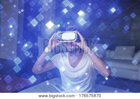 Young man with headset playing virtual reality with blue glowing suare tiles